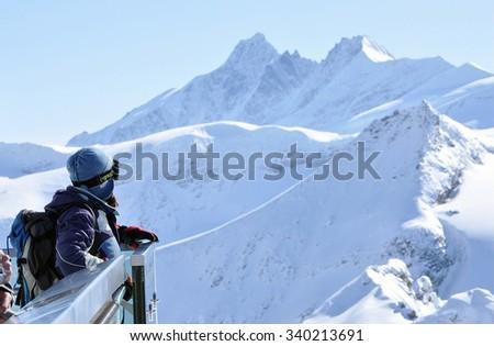 KITZSTEINHORN, AUSTRIA - MARCH 6, 2012: Unidentified skier woman admiring the winter landscape on a sightseeing platform in the mountains - stock photo