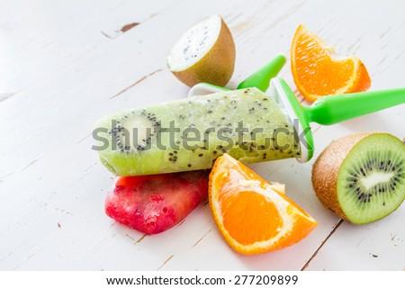 Kiwi and berry fruit ice pops, white wood background - stock photo