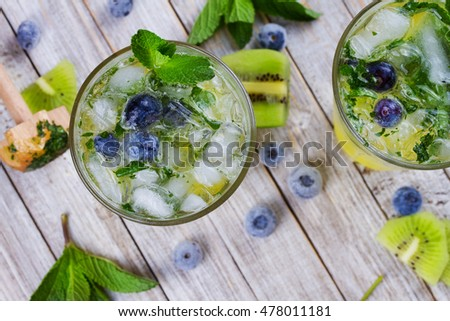 Kiwi and blueberry mojito.  Frozen summer berries cocktail. View from above, top studio shot