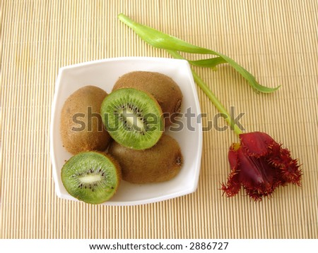 kiwi and red flower in plate - stock photo