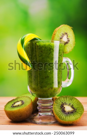 Kiwi cocktail glass on wooden table - stock photo