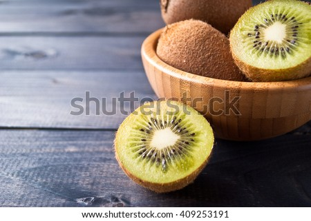 Kiwi fruit in a bowl on wooden background. Copy space - stock photo