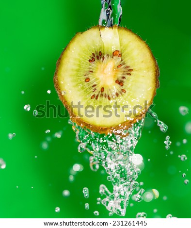 kiwi fruit in a spray of water on a green background - stock photo