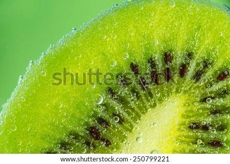 Kiwi fruit in water with bubbles over green background. - stock photo