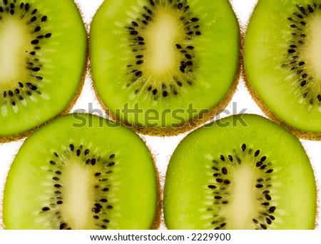 Kiwi fruit slices aligned on white background - stock photo