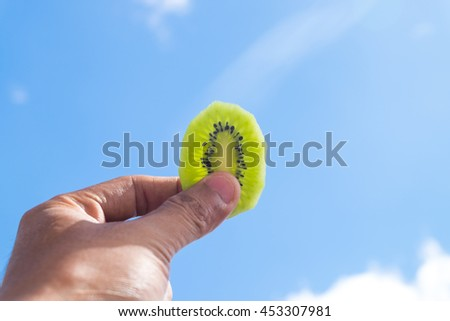 Kiwi fruit slide with hand holding on blue sky and cloud summer day with sun lighting - stock photo