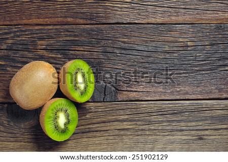 Kiwi fruit with half on dark wooden background, top view - stock photo