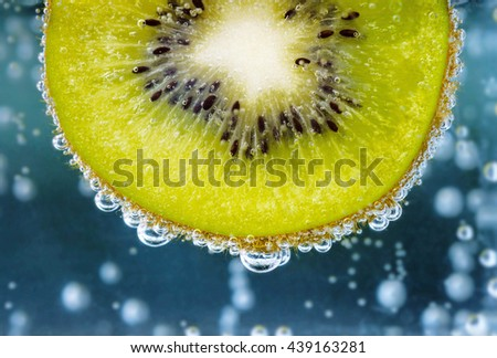 Kiwi in blue water with bubbles. - stock photo