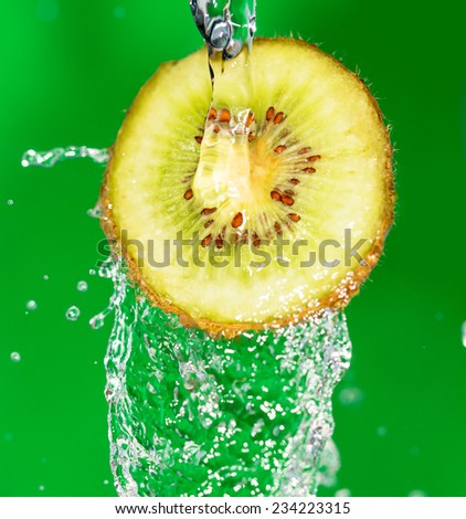 Kiwi in water on a green background - stock photo