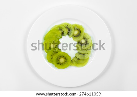 Kiwi in yogurt on white plate, view from above - stock photo