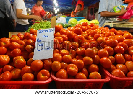 KL, MALAYSIA- JUNE 6, 2014 : Hawker stall selling fresh tomato at a night wet market in Kuala Lumpur, Malaysia. Outdoor market provide better income due to cheaper avenue and less fuzzy buyers.