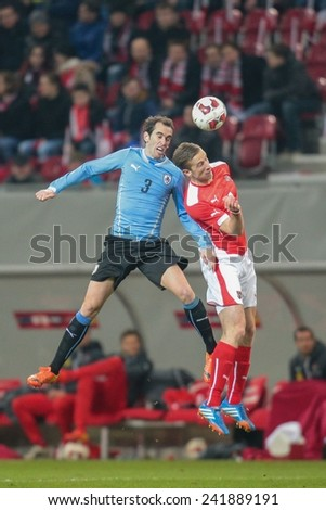 KLAGENFURT, AUSTRIA - MARCH 05, 2014: Diego Godin (#3 Uruguay) and Marc Janko (#21 Austria) fight for the ball in a friendly soccer game between Austria and Uruguay. - stock photo