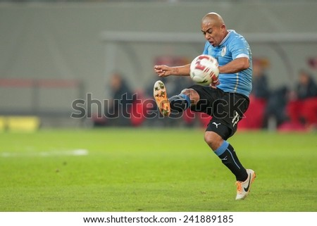 KLAGENFURT, AUSTRIA - MARCH 05, 2014: Egidio Arevalo R�­ios (#17 Uruguay) kicks the ball in a friendly soccer game between Austria and Uruguay. - stock photo