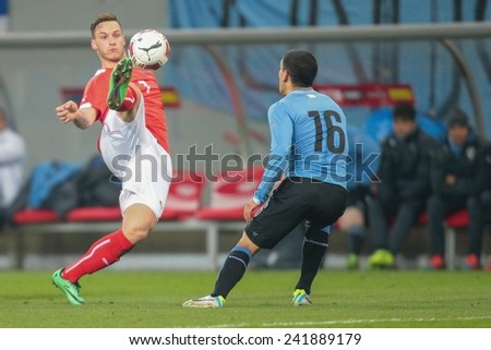 KLAGENFURT, AUSTRIA - MARCH 05, 2014: Marko Arnautovic (#7 Austria) and Maximilano Pereira (#16 Uruguay) fight for the ball in a friendly soccer game between Austria and Uruguay. - stock photo