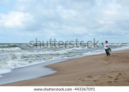 KLAIPEDA, LITHUANIA - JULY 11, 2015: Elderly woman on shore of restless Baltic Sea photographs landscape