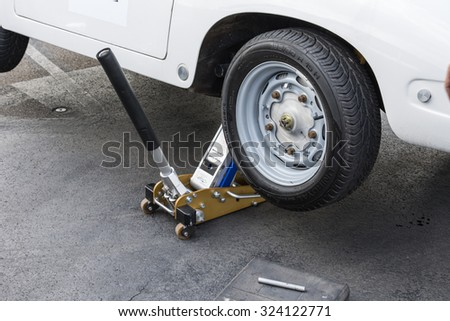 KLETTWITZ, GERMANY - September 26 2015: Man placing a hydraulic jack under his car to raise the vehicle allowing - stock photo