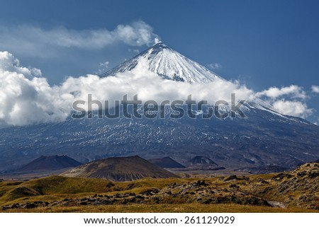 Kliuchevskoi Volcano (Klyuchevskaya Sopka) is a stratovolcano, the highest mountain on Kamchatka Peninsula of Russia, the highest active volcano of Eurasia. Beautiful view of the volcano on sunny day. - stock photo