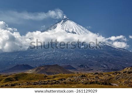 Klyuchevskoi Volcano (Klyuchevskaya Sopka) is a stratovolcano, the highest mountain on Kamchatka Peninsula of Russia, the highest active volcano of Eurasia. Beautiful view of the volcano on sunny day. - stock photo