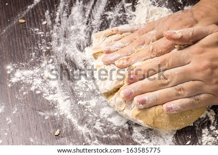 Kneading dough on wooden board - stock photo