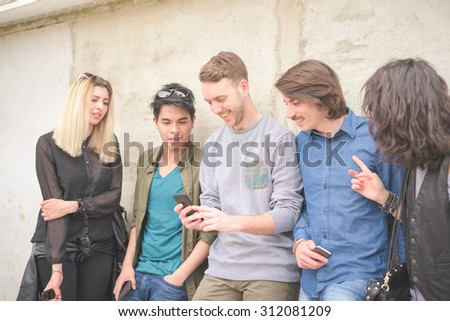 Knee figure of a group of young multiethnic friends leaning on a wall chatting to each other having fun using smartphone - social network,technology, communication, technology concept  - stock photo