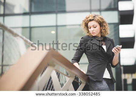 Knee figure of a young beautiful caucasian contemporary businesswoman leaning on a railing using smartphone and tablet looking down on the screen - technology, network, business, finance concepts - stock photo