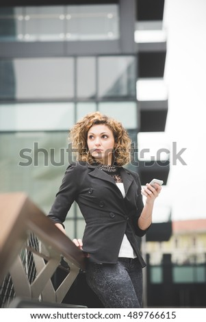 Knee figure of a young beautiful caucasian contemporary businesswoman leaning on a railing using smartphone and tablet overlooking - technology, network, business, finance concepts