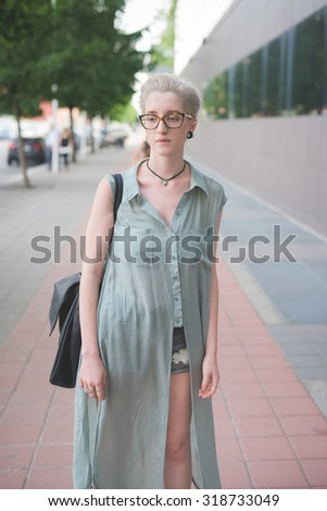 Knee figure of a young handsome caucasian blonde italian designer posing in the city, overlooking right - wearing an azure dress - seriousness, pensive concept