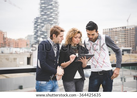 Knee figure of multiracial business people working outdoor in town. She is holding a tablet connected online, all looking down the screen - business, work, technology concept - stock photo