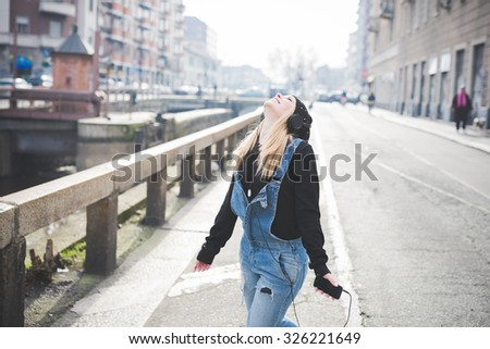 Knee figure of young beautiful blonde straight hair woman in the city with headphones listening to music, arms wide open, feeling free, laughing - freedom, happiness concept - stock photo