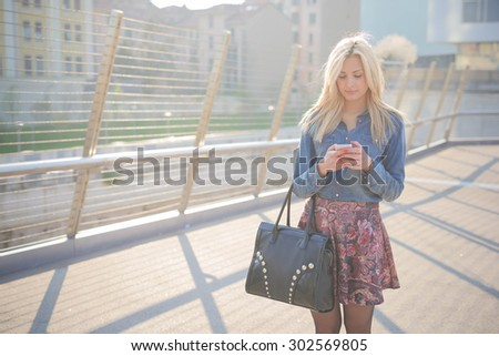 Knee figure of young beautiful caucasian blonde girl using a smartphone wearing a jeans shirt, a bag and a floral skirt looking downward the screen - technology, communication, social network concept - stock photo