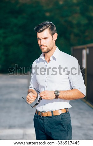Knee figure of young handsome caucasian black hair modern businessman posing in the city, overlooking right, serious - working, business, successful concept - stock photo