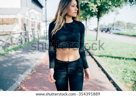 Knee figure of young handsome caucasian blonde straight hair woman model posing outdoor in the city, overlooking left, serious - pensive, thinking future concept - stock photo