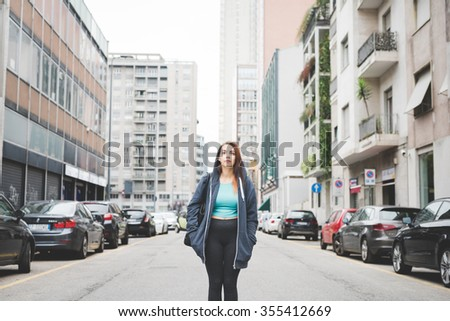 Knee figure of young handsome caucasian reddish straight hair woman posing on the middle of the street, hands in pocket, looking upward, pensive - thoughtful, thinking future concept - stock photo