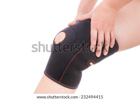 Knee injury. Girl holds hands bandage on his leg. - stock photo