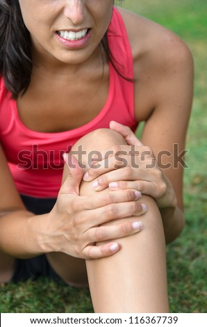 Knee injury pain. Painful sport injury. Female athlete grabbing leg because of lesion after running. - stock photo