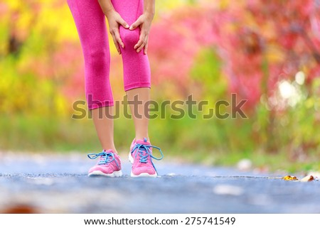 Knee Injury - running sport knee injuries on woman. Female runner with pain from sprain knee. Close up of legs, muscle and knee outdoors in forest. - stock photo