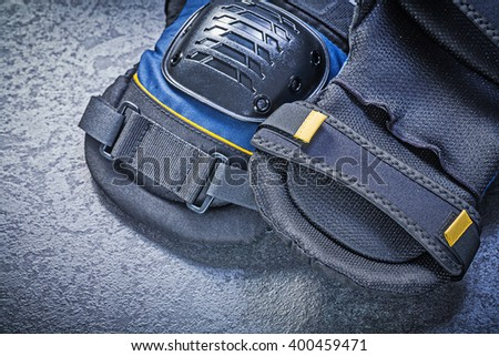 Knee pads on black background directly above construction concept. - stock photo