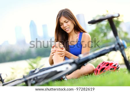 Knee pain bike injury. Woman with pain in knee joints after biking on bicycle. Girl sitting down with painful face expression. Mixed race sport fitness model outdoors. - stock photo