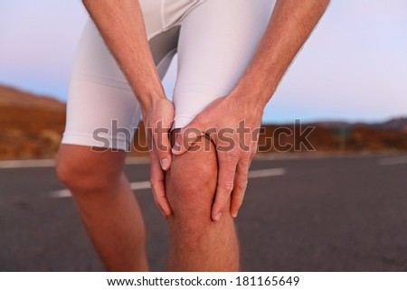 Knee pain - man with running sport injury. Male runner having knee problems during exercise outside. - stock photo