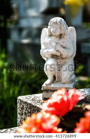 Kneeling angel statue, at a tomb - stock photo