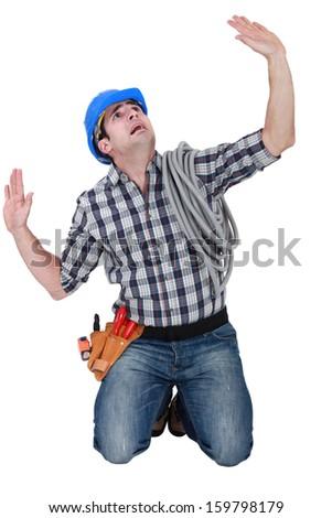Kneeling laborer looking afraid - stock photo