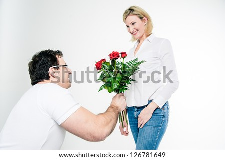 Kneeling man gives roses to his girlfriend - stock photo
