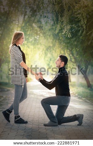 Kneeling Man Proposing with an Engagement Ring - Man proposing marriage with a romantic gesture - stock photo