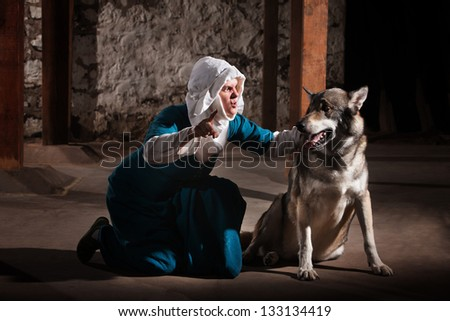 Kneeling middle ages nun character giving commands to a dog - stock photo