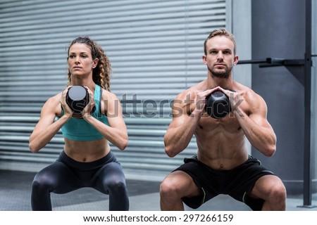 Kneeling muscular couple exercising with kettlebells - stock photo