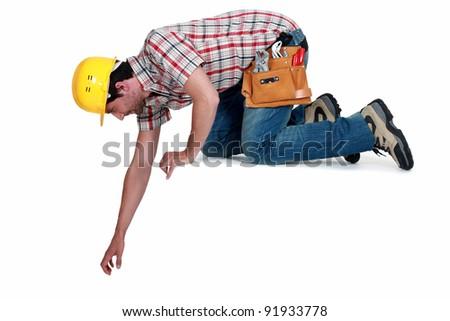 Kneeling workman, isolated on white background - stock photo