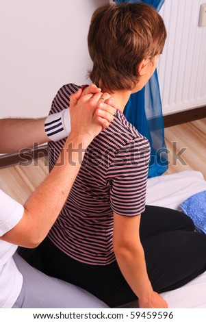 Kneeling young woman gets back massage at yumeiho session - stock photo