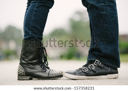 Knees down photo of a couple in an embrace facing each other in jeans and bad ass leather shoes. - stock photo