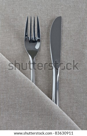 Knife and fork as a place setting on natural linen