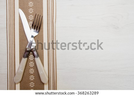 knife and fork at napkin on white wooden background - stock photo